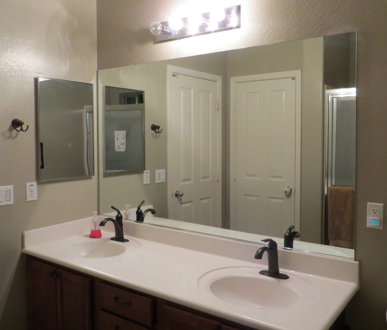 complete old fashioned bathroom with wooden vanity and white sinks under clear framed bathroom mirrors