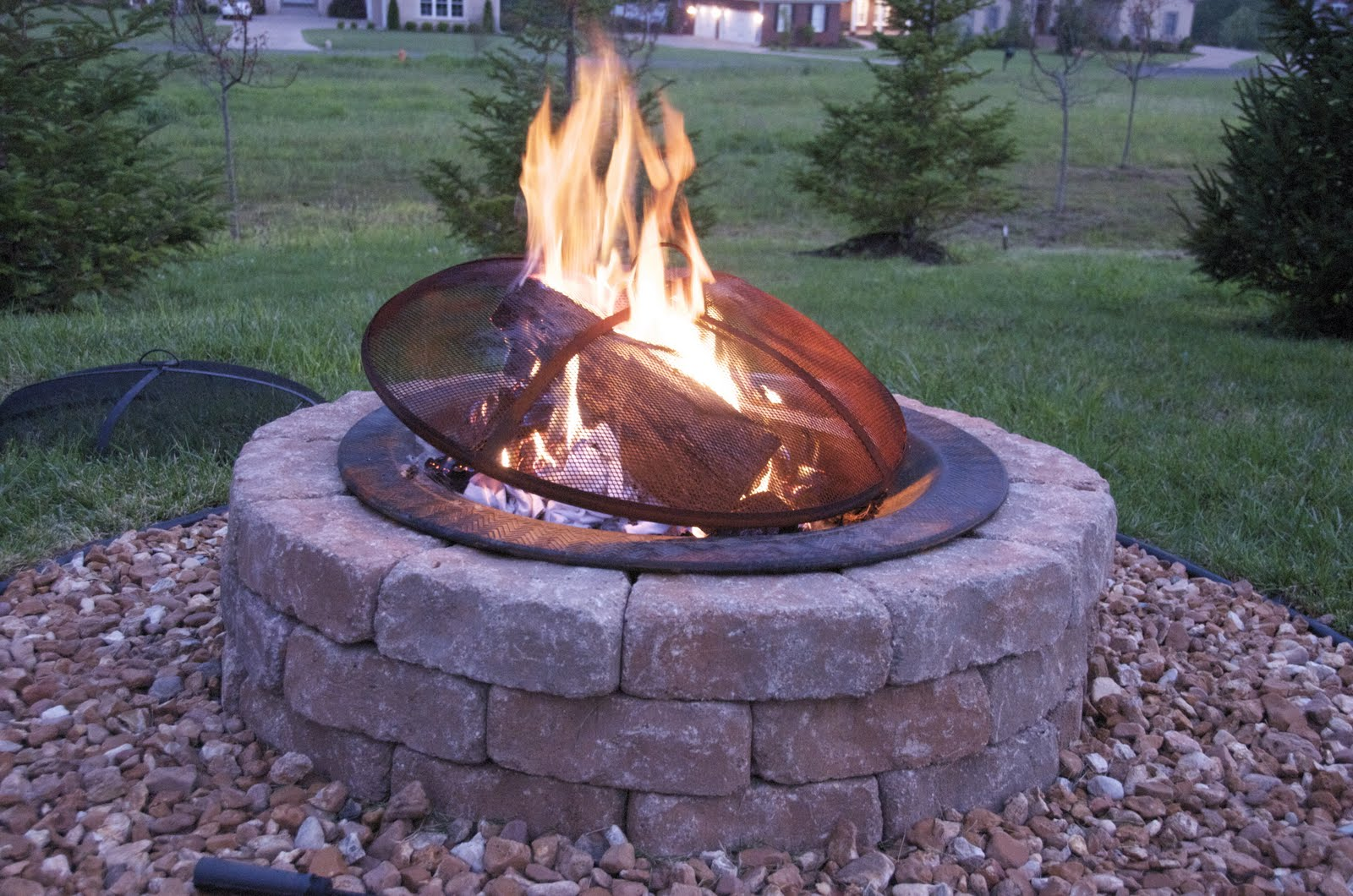 Complete Round Stone Fire Pit Designs with Metal Cover near Green Grass Yard