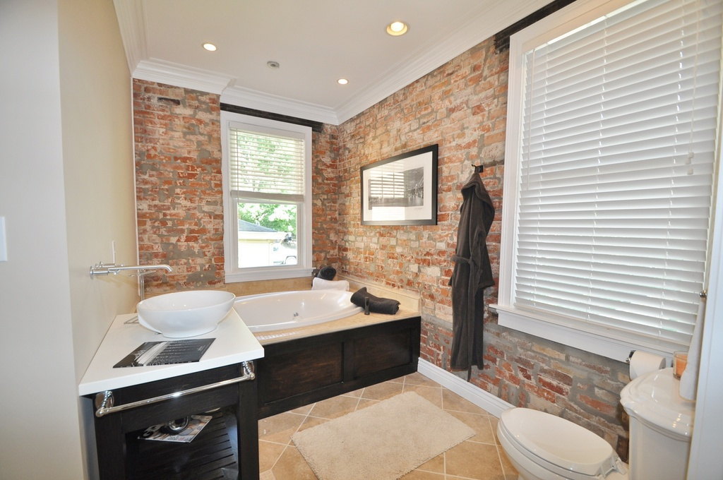 Complete Tiny Bathroom With Exposed Brick Wall And Crown Molding Ideas Near Black Vanity