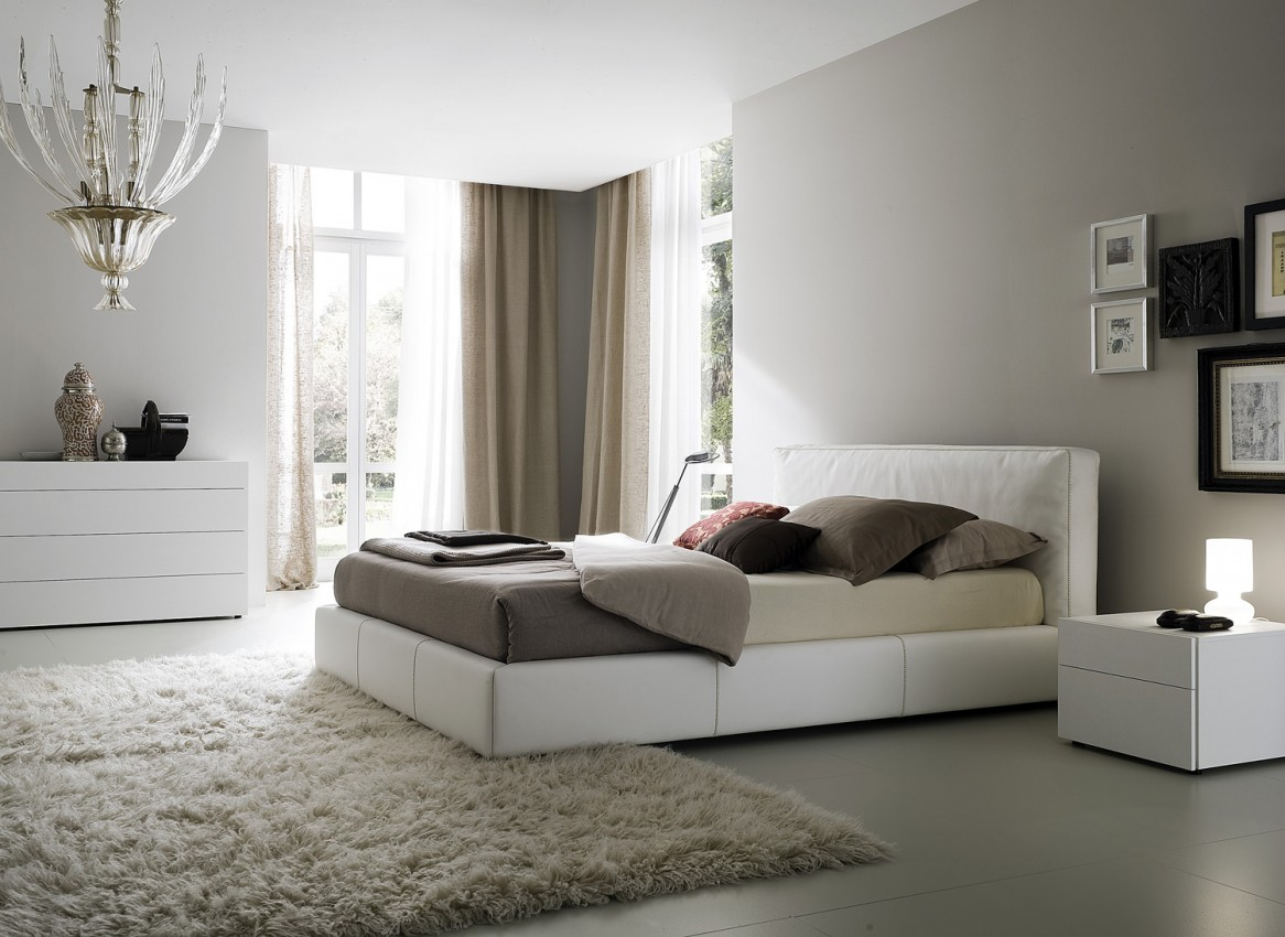 Complete Wide Bedroom using White Bed and Small Side Table near Carpet Flooring under Oversized Lamp
