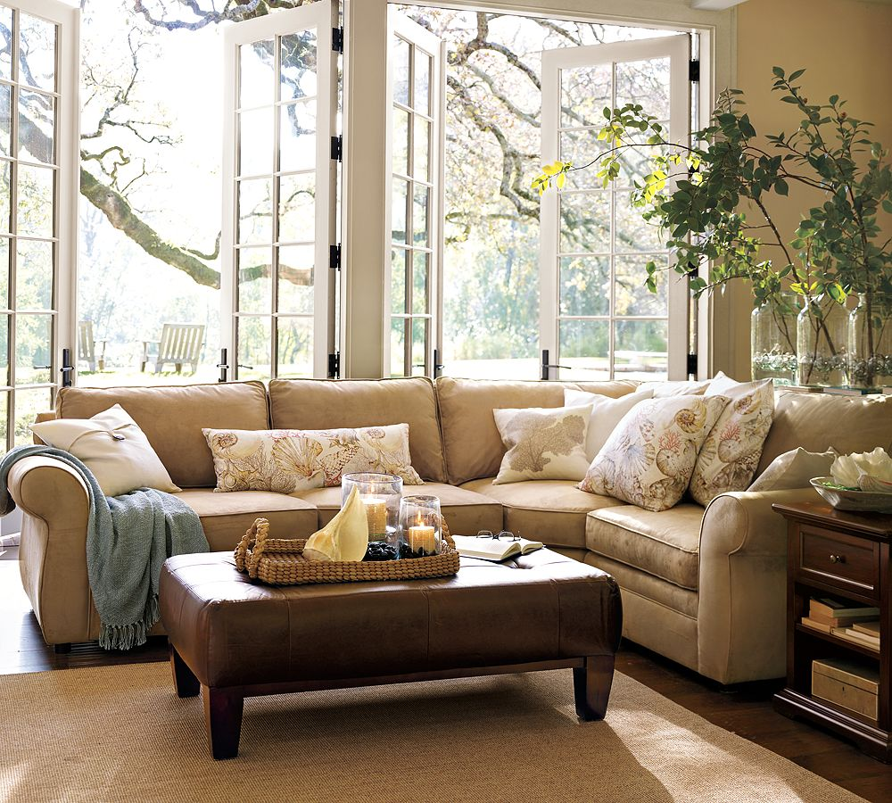 Cream Sectional Pottery Barn Sofa and Leather Ottoman near Wooden Side Table in Cozy Room