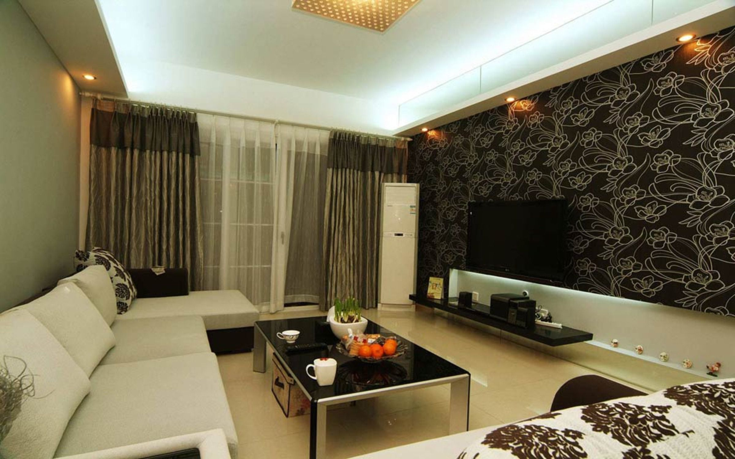 Decorate Living Room Design Ideas with Flowery Wallpaper and Black Coffee Table near Grey Sectional Sofa