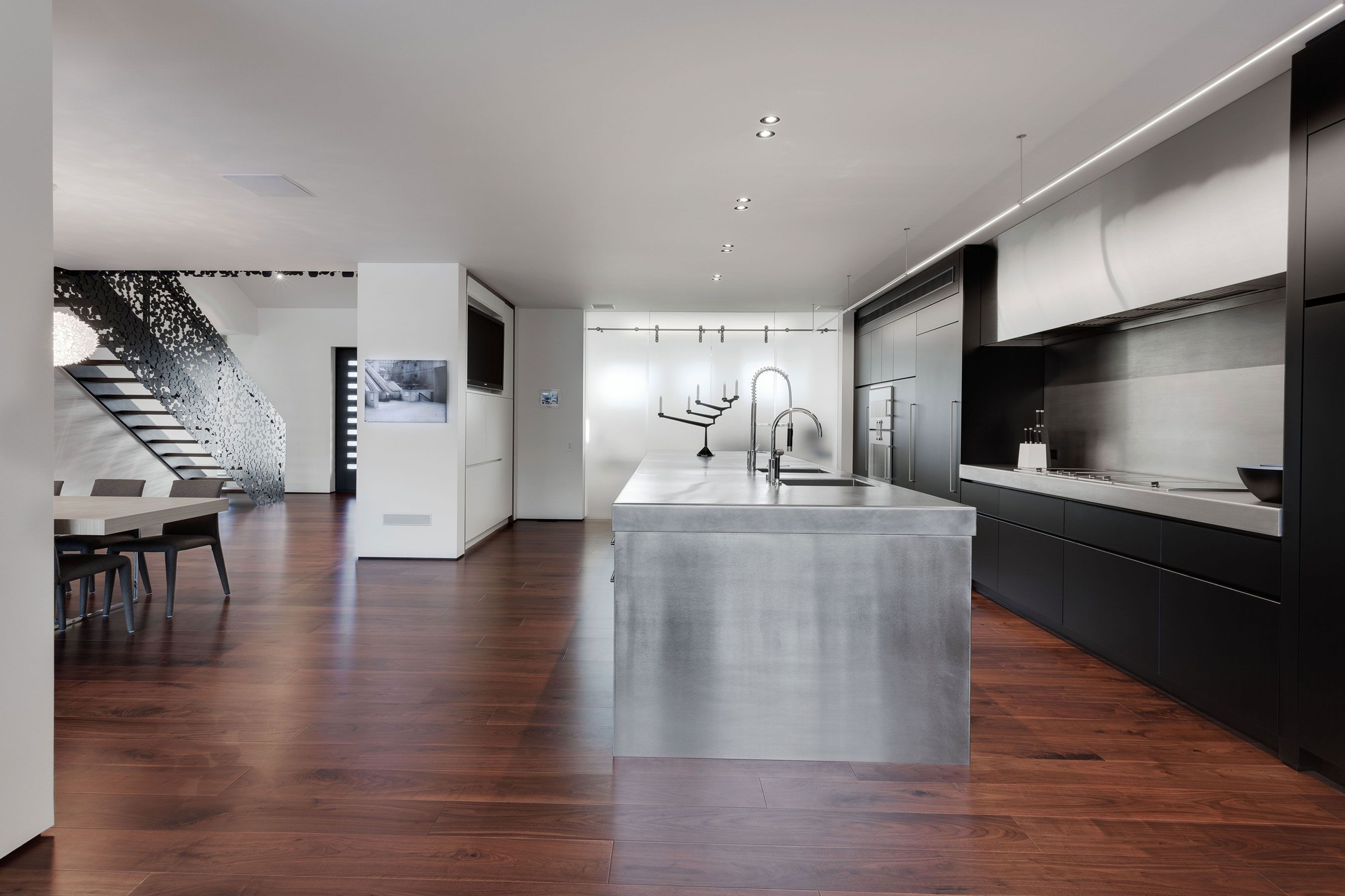 Decorate Open Kitchen with Black Counter and Long Stainless Steel Kitchen Island on Laminate Teak Flooring