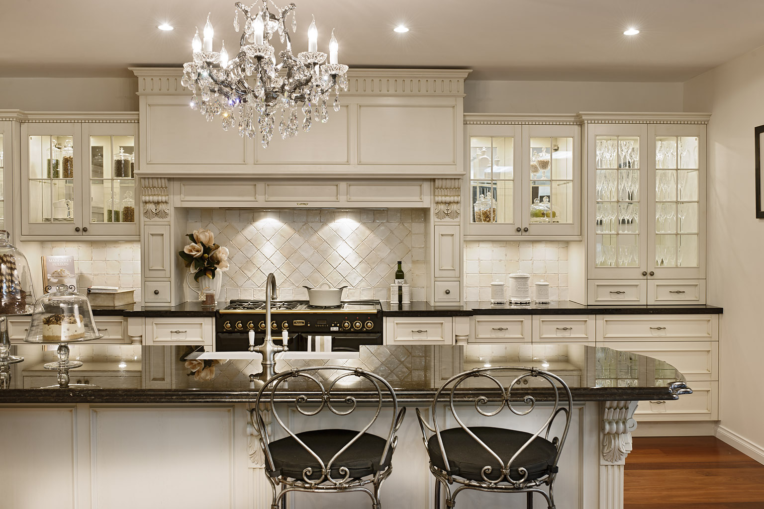 Elegant Crystal Chandelier above Classic Island and Classic Metal Stools for Country Kitchen Ideas