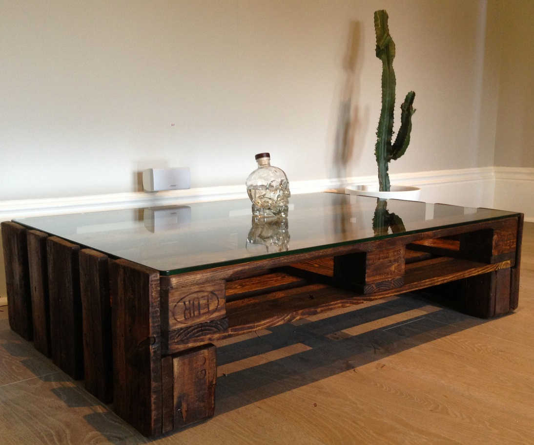 Glass Top Large Coffee Table Placed in Contemporary Room with Hardwood Flooring and White Wall