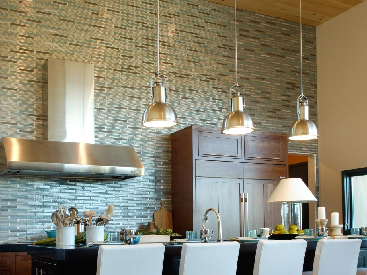 Glossy Ceiling Lamps Installed above Long Black Island and White Stools facing Appealing Kitchen Tile Backsplash
