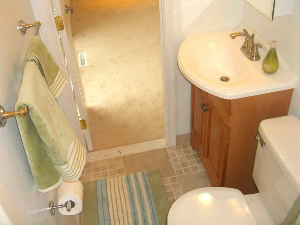 Glossy Towel Hanger and Wooden Vanity Completing Small Bathroom Design with Tile Flooring and White Door