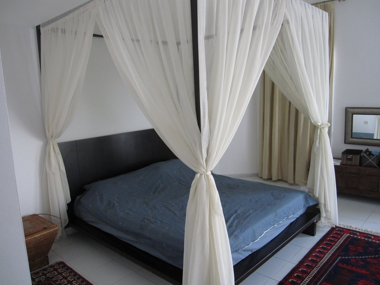 Grey Bedding and Sheer Curtain Completing Dark DIY Canopy Bed on White Tile Flooring near White Wall