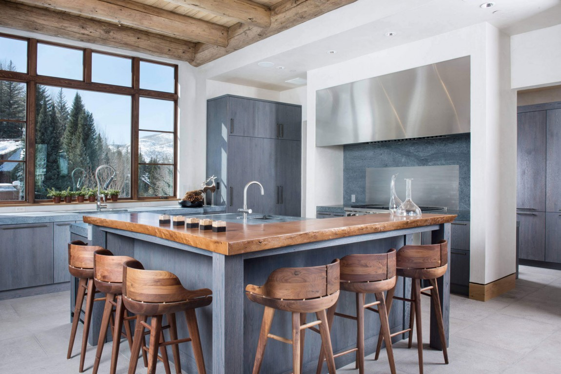 Grey Cabinets and Wide Kitchen Islands with Seating in Unique Kitchen using Concrete Flooring