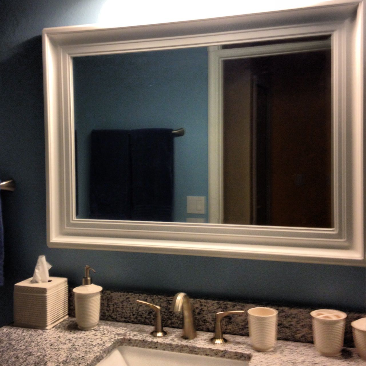 Grey Granite Top and White Sink Located under White Framed Bathroom Mirrors on Grey Painted Wall