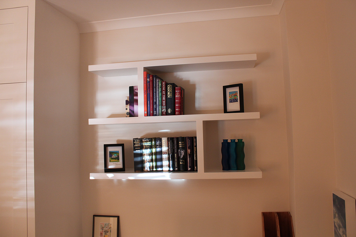 High Wardrobe Cabinet and White Floating Shelves Completing Simple Room with White Painted Wall