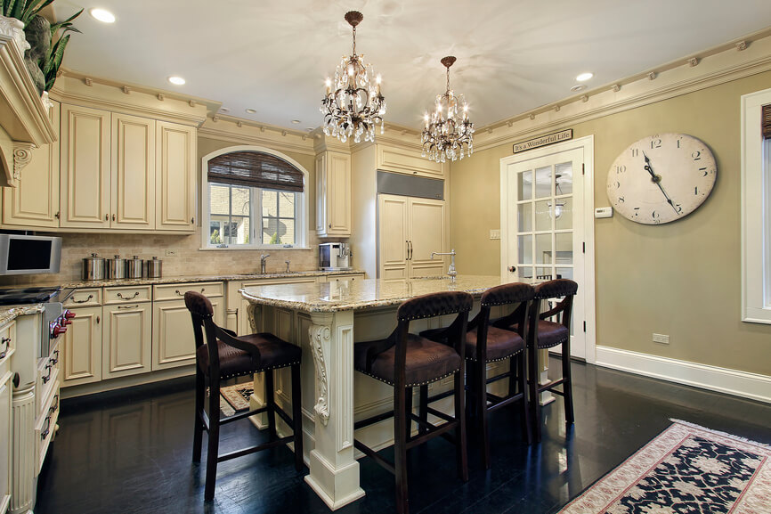 Impressive Crystal Chandelier above White Kitchen Islands with Dark Seating facing Classic White Counter