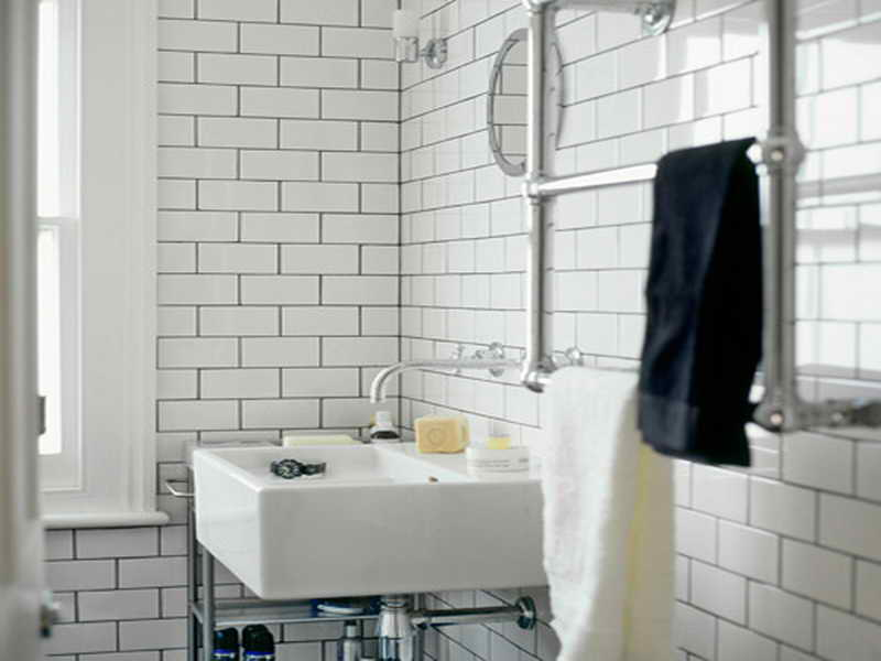 Industrial Themed Bathroom with White Sink and Glossy Towel Handles on White Subway Tile Bathroom Wall