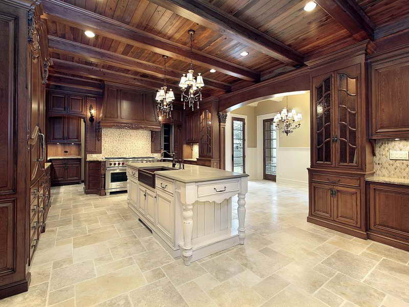 Install Classic Chandeliers above White Island in Gorgeous Kitchen with Stone Kitchen Floor Tile