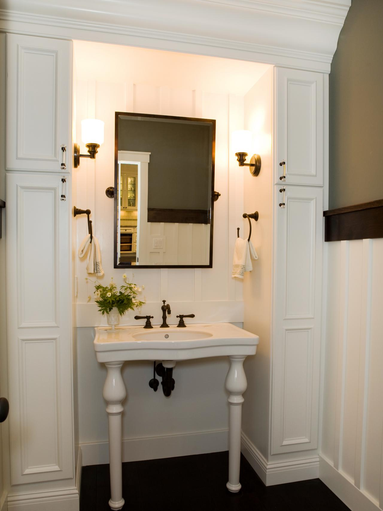Install Classic Wall Lamps Above White Pedestal Sink Storage In  Traditlional Bathroom With Wooden Flooring