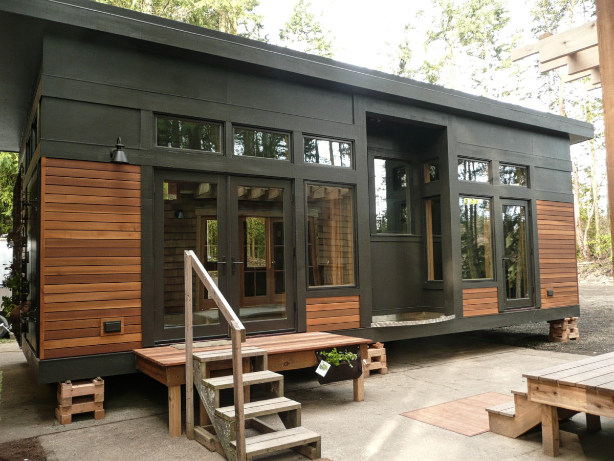 Install Wooden Stairs and Deck for Dark Small Prefab Homes with Glass Windows and Wooden Wall