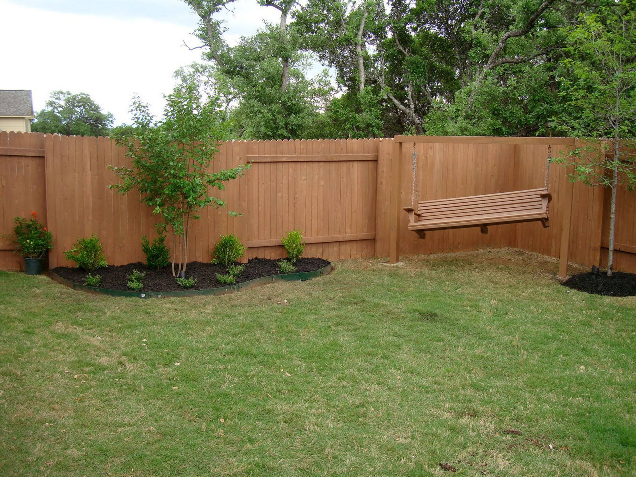 Interesting Wooden Fence also Hanging Chair plus Plants and Grasses