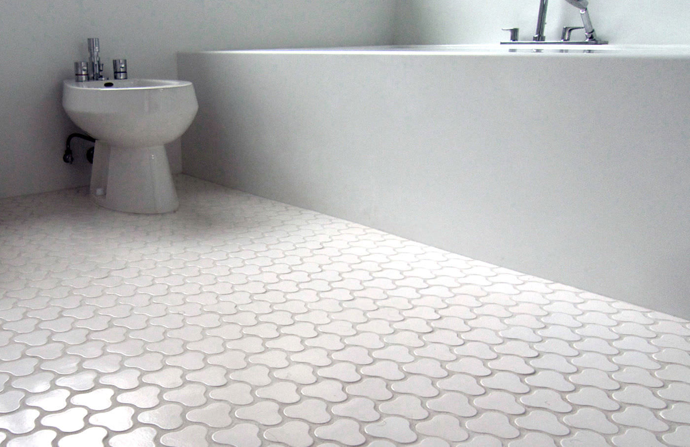 Minimalist Bathroom with Long Bathtub and Toilet on Unique Bathroom Floor Tile near Grey Wall