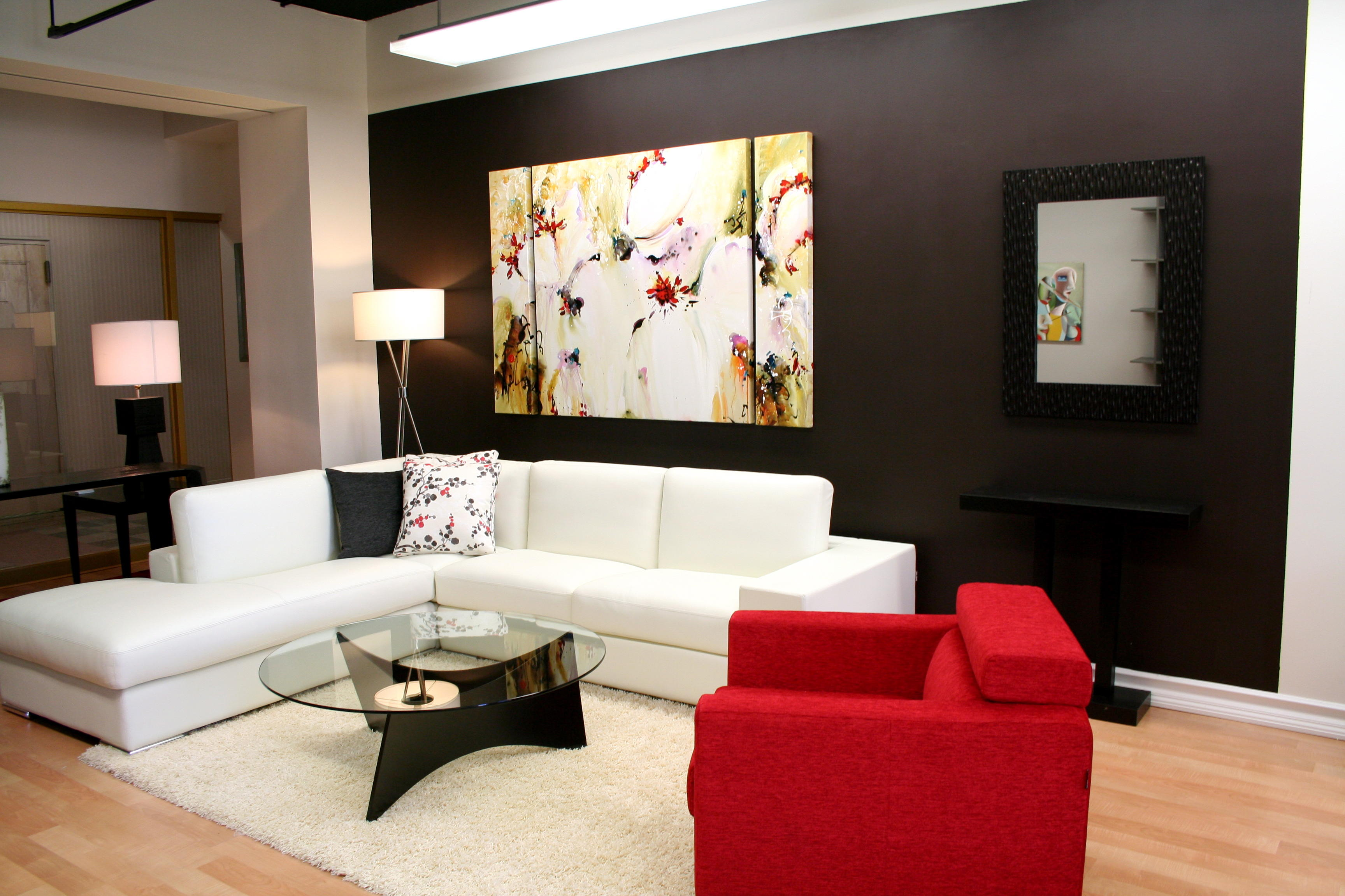 Modern Living Room with Interesting Wall Decorating Ideas and White Sectional Sofa facing Glass Top Coffee Table
