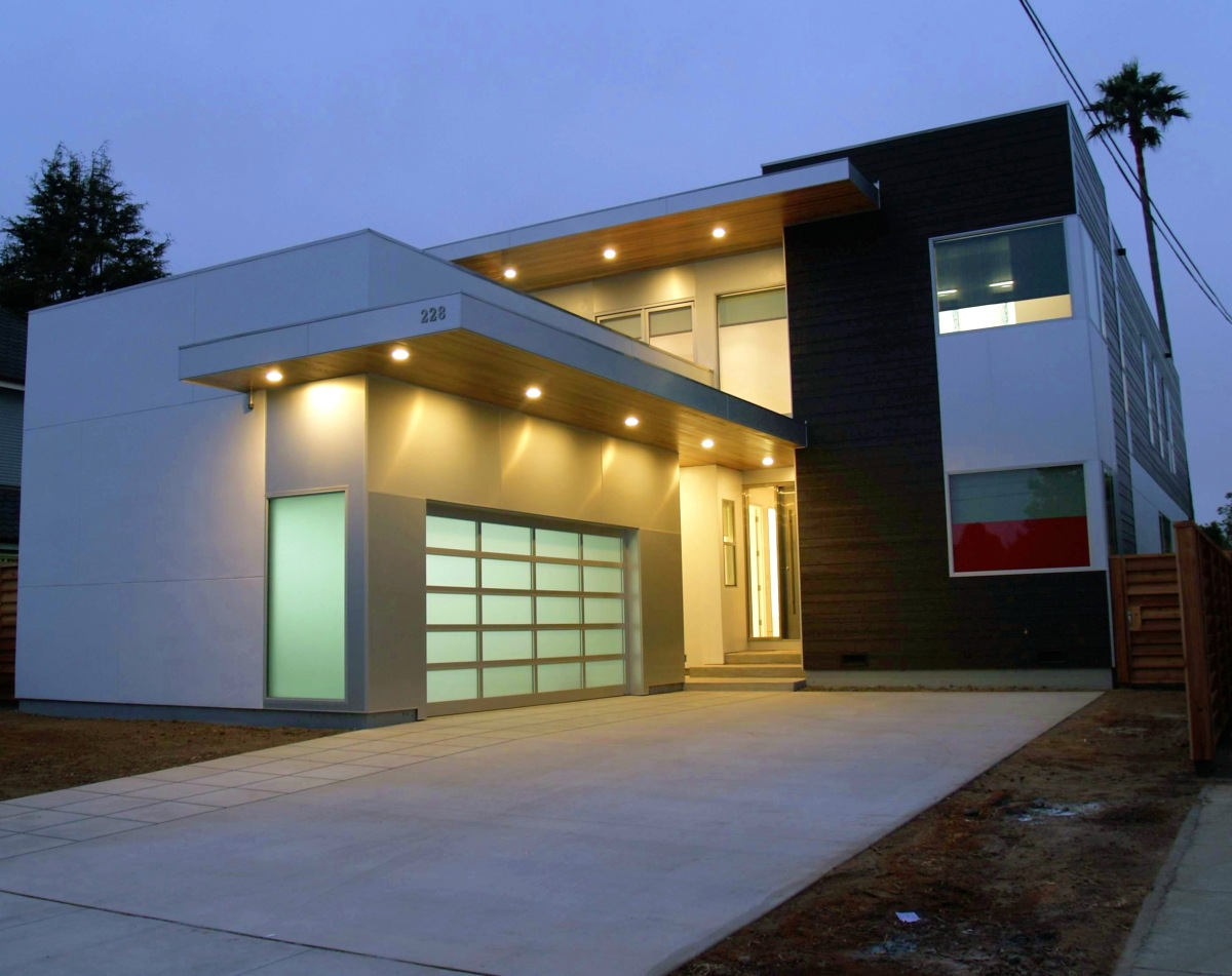 Modern Prefab Homes Front Exterior with Bright Lighting and Wide Garage Door facing Concrete Pathway