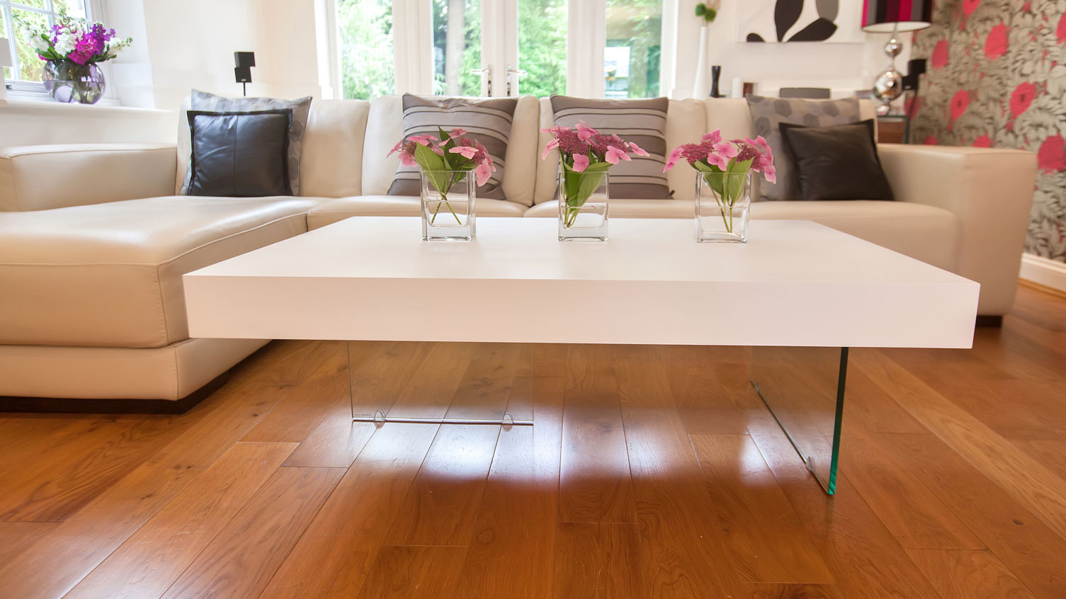 Pink Flowers on White Large Coffee Table near Modern Sectional Sofa on Laminate Teak Flooring