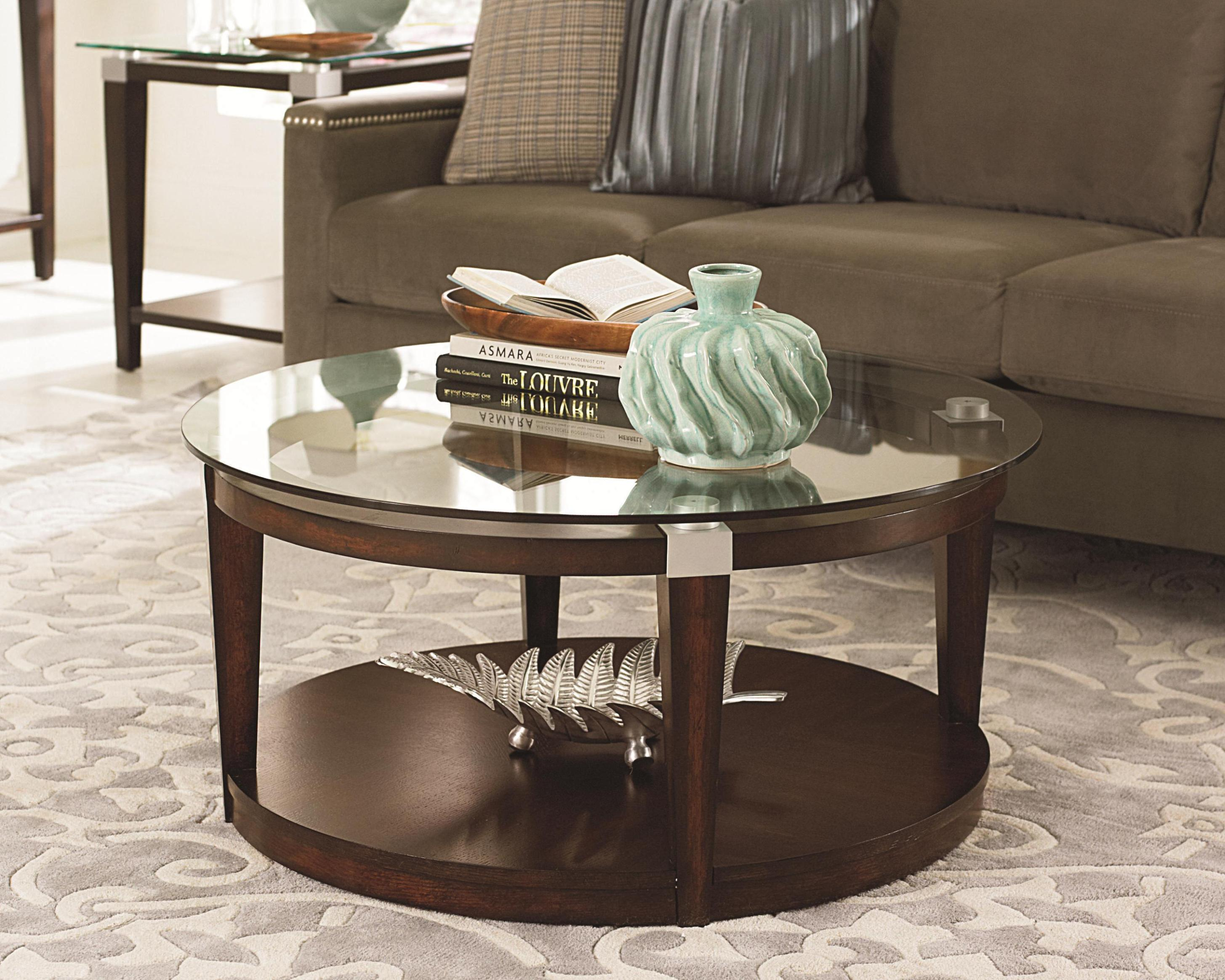 Place Antique Ornaments on Simple Oak Round Glass Coffee Table inside Comfy Sitting Room with Long Sofa
