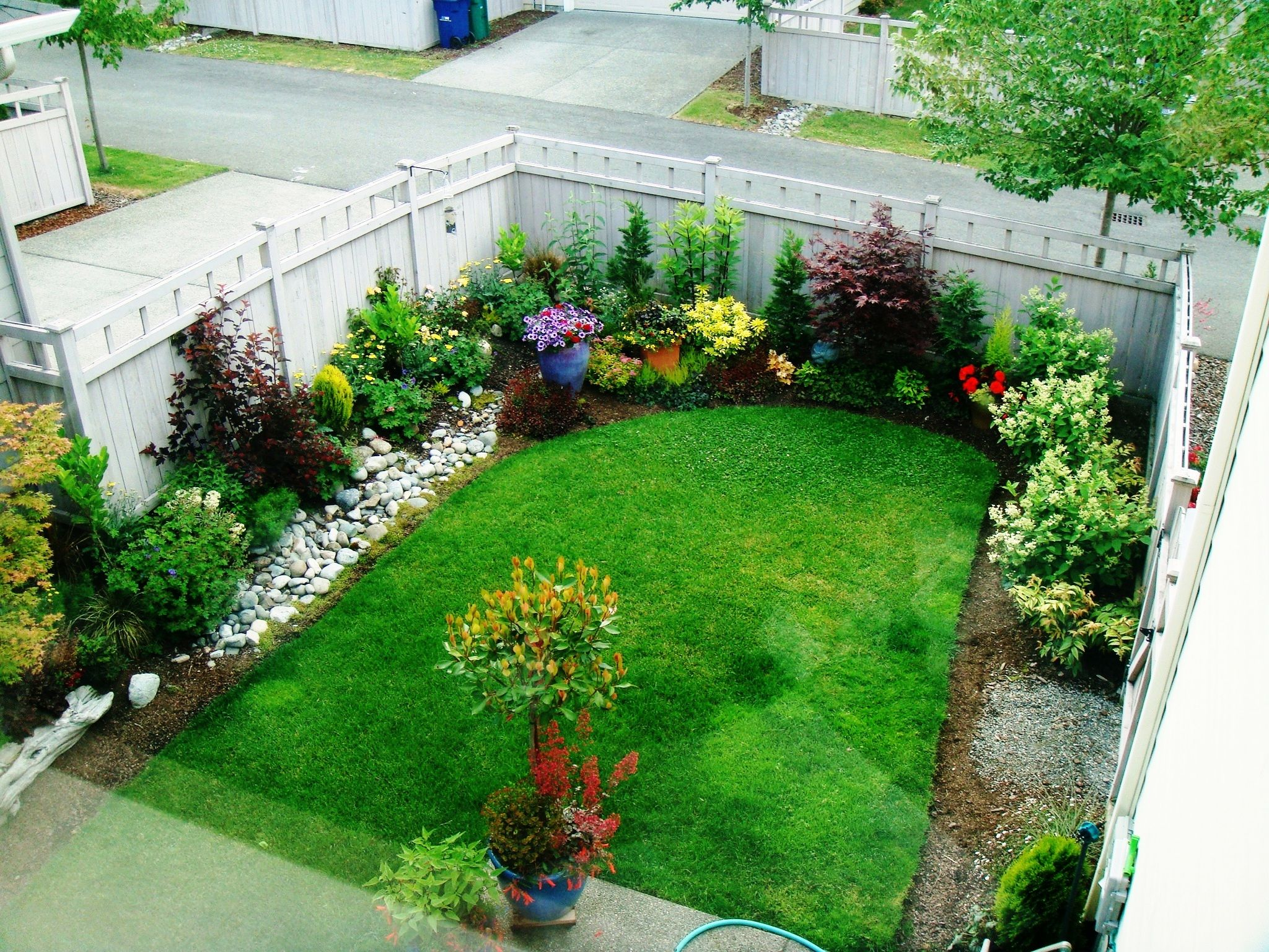 Place Colorful Flowerss and Plants in Old Fashioned Small Garden Ideas with White Oak Fence