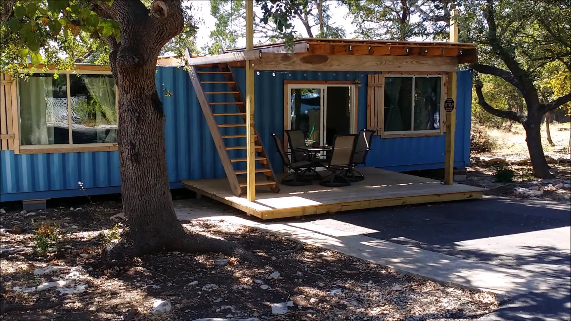 Place Metal Chairs and Table on Small Deck of Cargo Container Homes with Wooden Stairs and Blue Wall