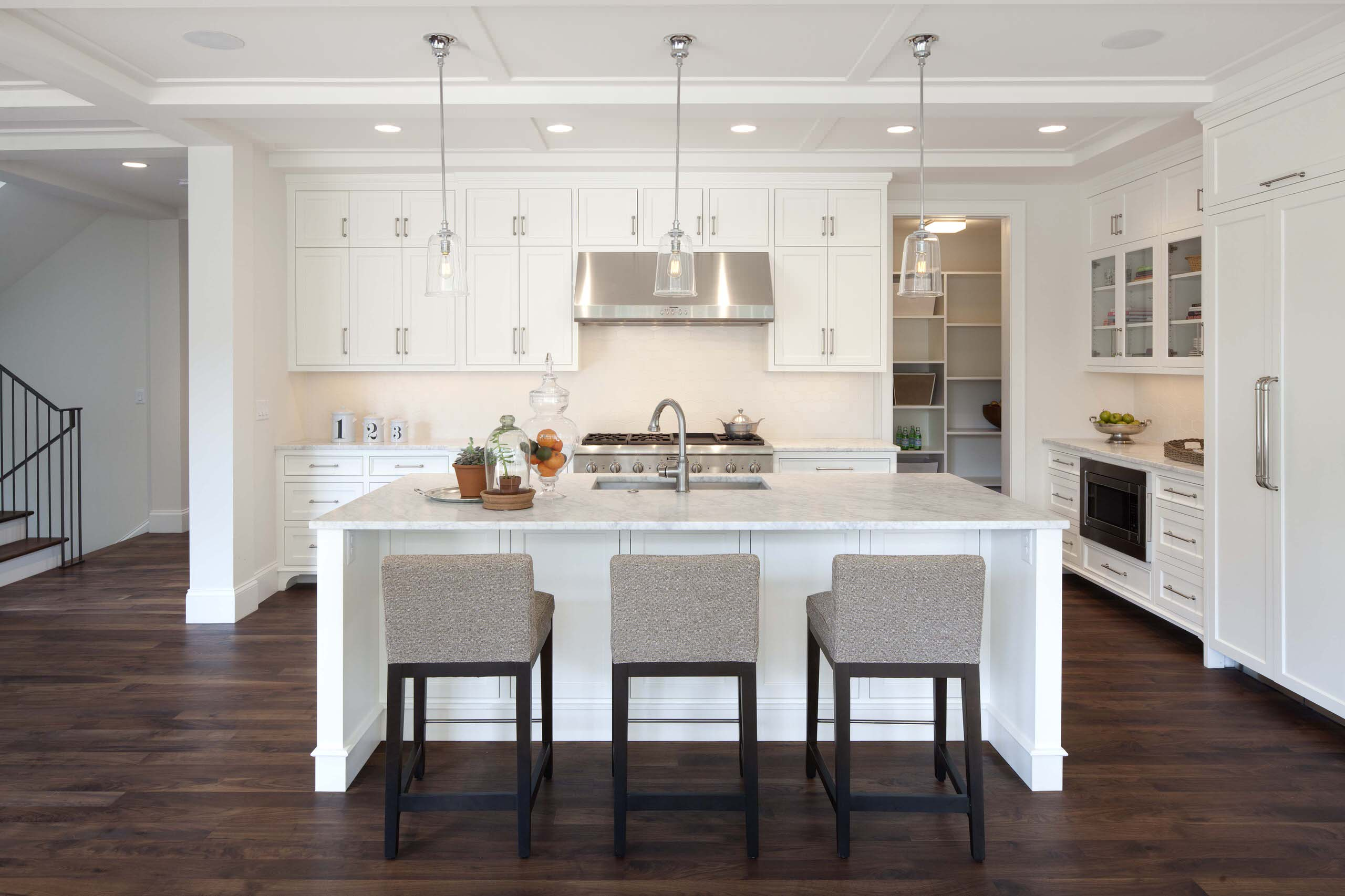 Place Minimalist White Kitchen Island with Grey Lather Stools on Hardwood Flooring near White Cabinets