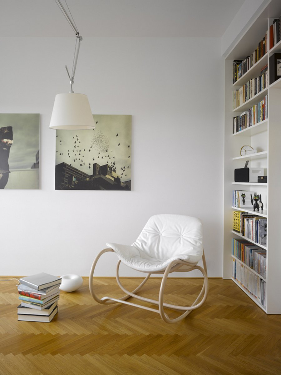 Place Modern White Rocking Chair in Open Home Library with White Bookshelves on Oak Flooring