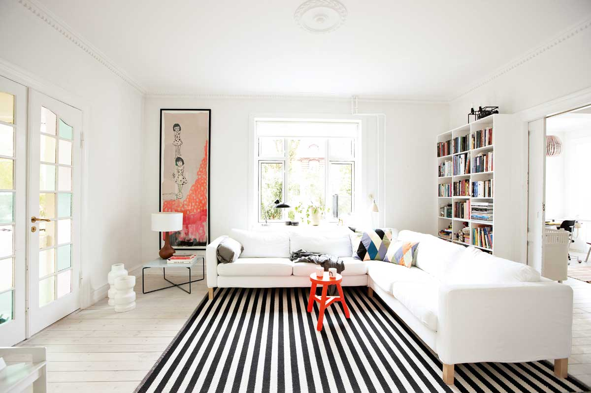 Place Red Round Table and White Sectional Sofa on Black and White Rug for Simple Room