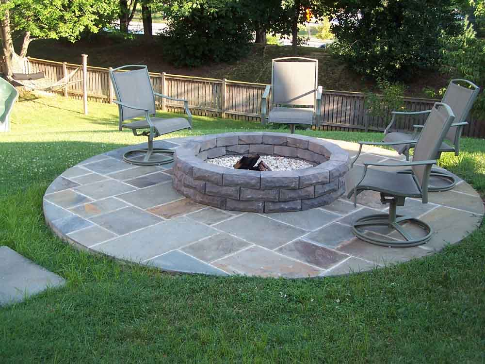 Place Round Grey Stone Fire Pit Designs and Metal Chairs on Stone Flooring beside Grass Yard