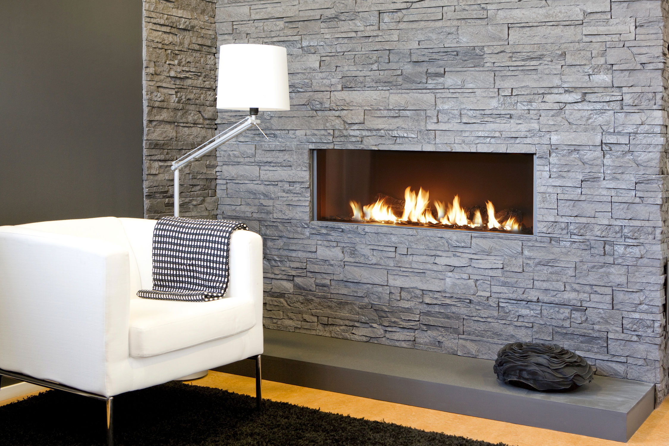 Place White Sofa and Modern Floor Lamp on Black Carpet Rug beside Stylish Stacked Stone Fireplace