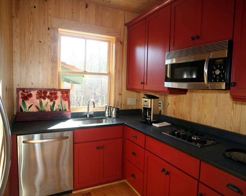 Small Kitchen Design with Red Cabinets and Counter near Wooden Backsplash and Dark Countertop