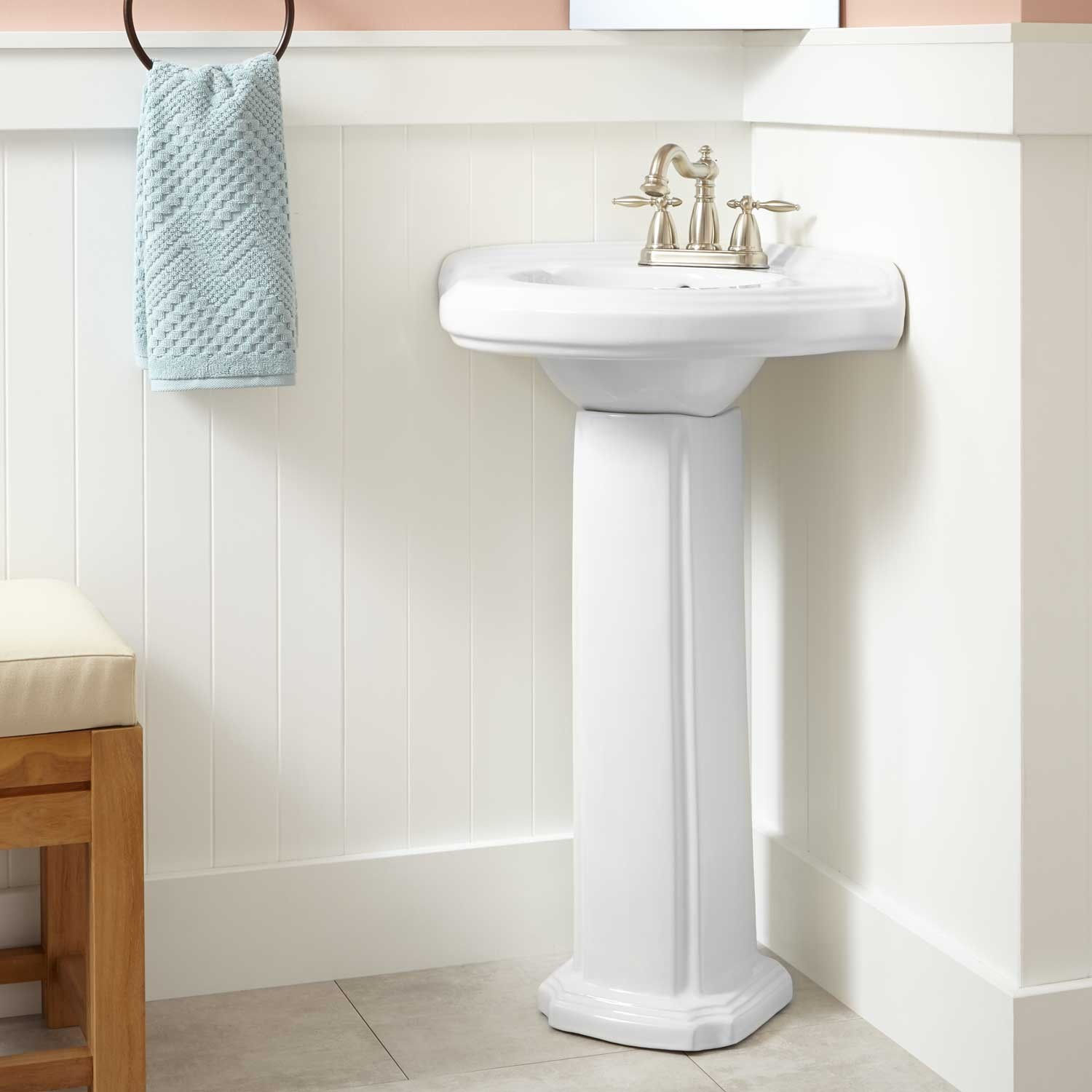 Small Pedestal Sink Storage in the Cozy Bathroom with Wooden Bench and Towel Hanger
