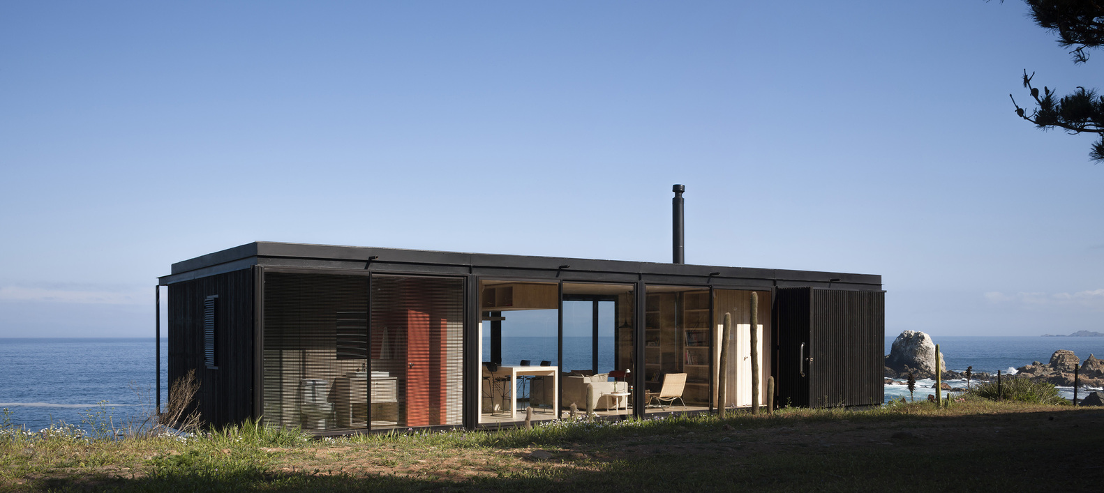 Small Prefab Homes Design with Wide Glass Sliding Door and Flat Roof facing Blue Sea