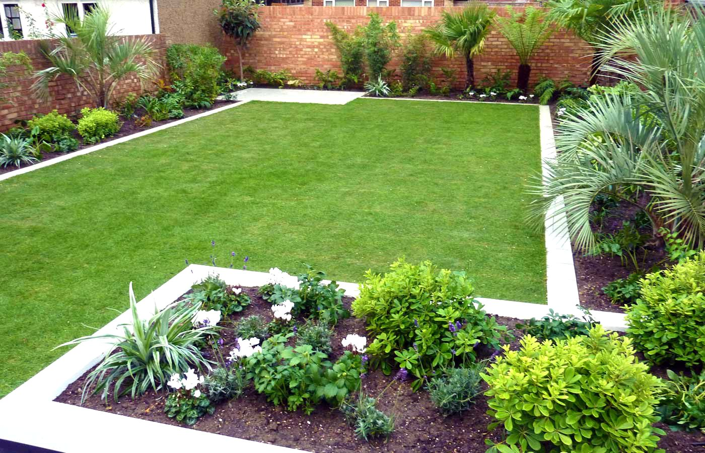 The Small Garden Ideas With Green Grass And Plants Near Exposed Brick Wall  Fence