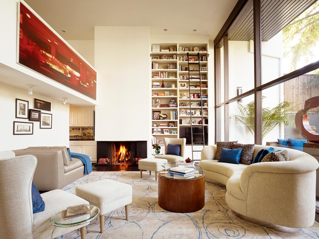The Wonderful Living Room Layout with Curve Sofa and High Wall Bookshelves near Modern Fireplace