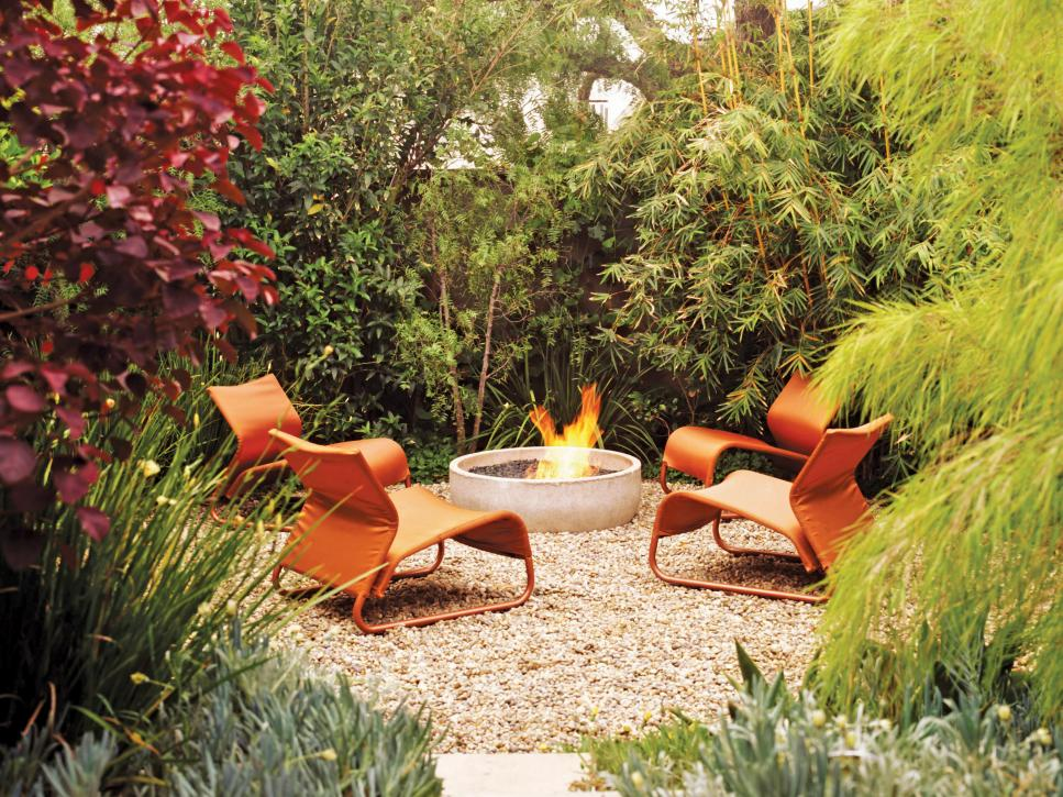 Use Interesting Fire Pit Designs to Complete Cozy Patio with Orange Chairs and Pebble Flooring