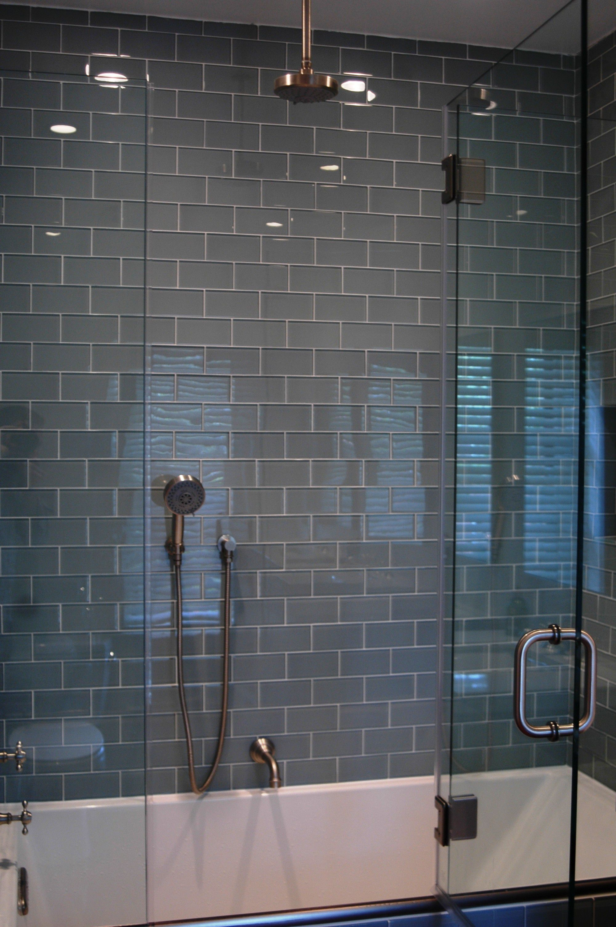 White Bathtub and Glass Shower Door under Glossy Faucet near Grey Subway Tile Shower
