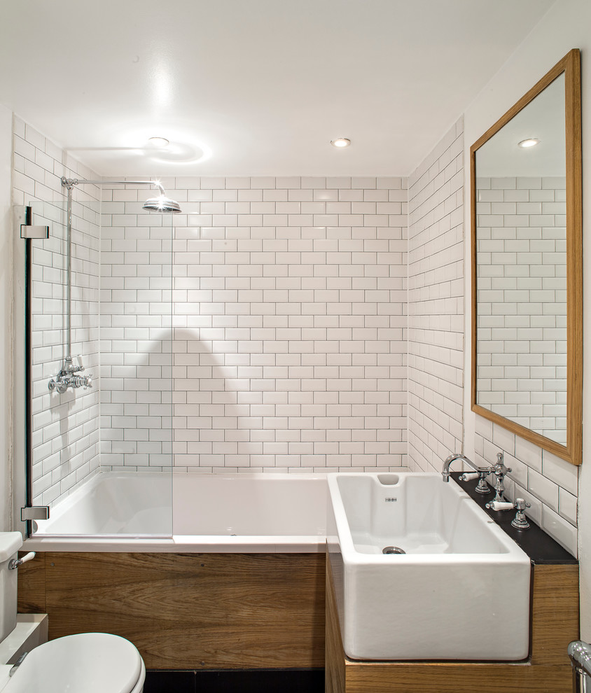 White Sink and Wooden Vanity Used inside Small Bathroom with Clean White Subway Tile Bathroom