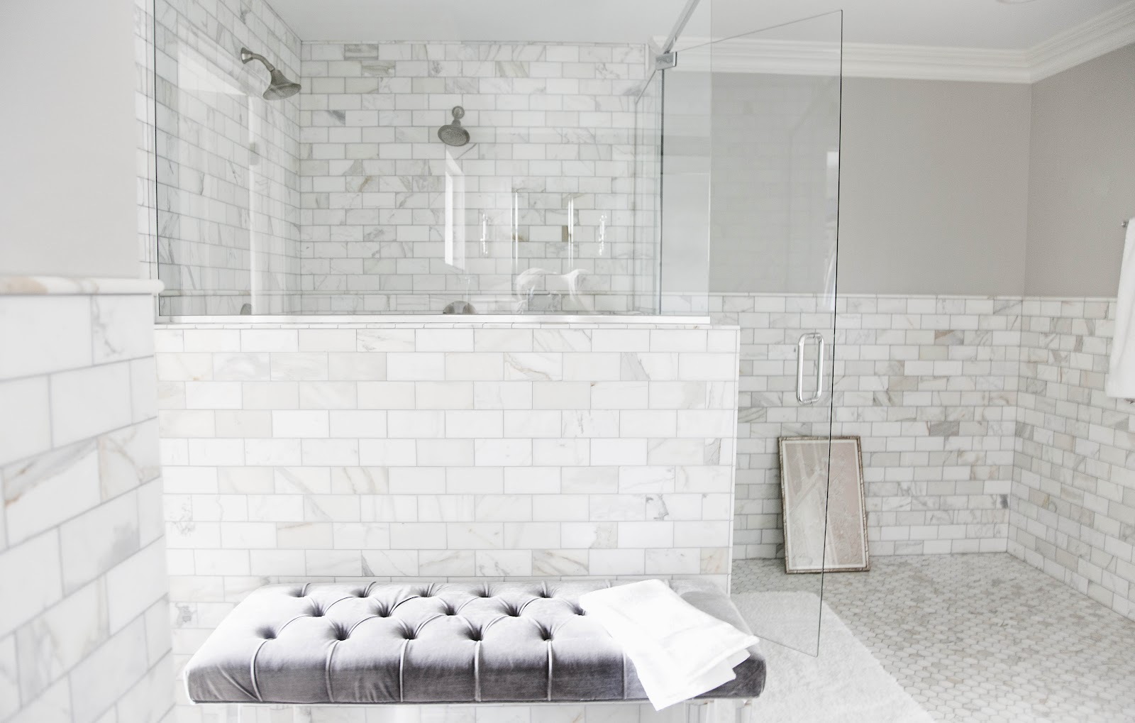 Wide Glass Shower Room and Grey Tufted Bench Placed near Marble Subway Tile Bathroom Wall