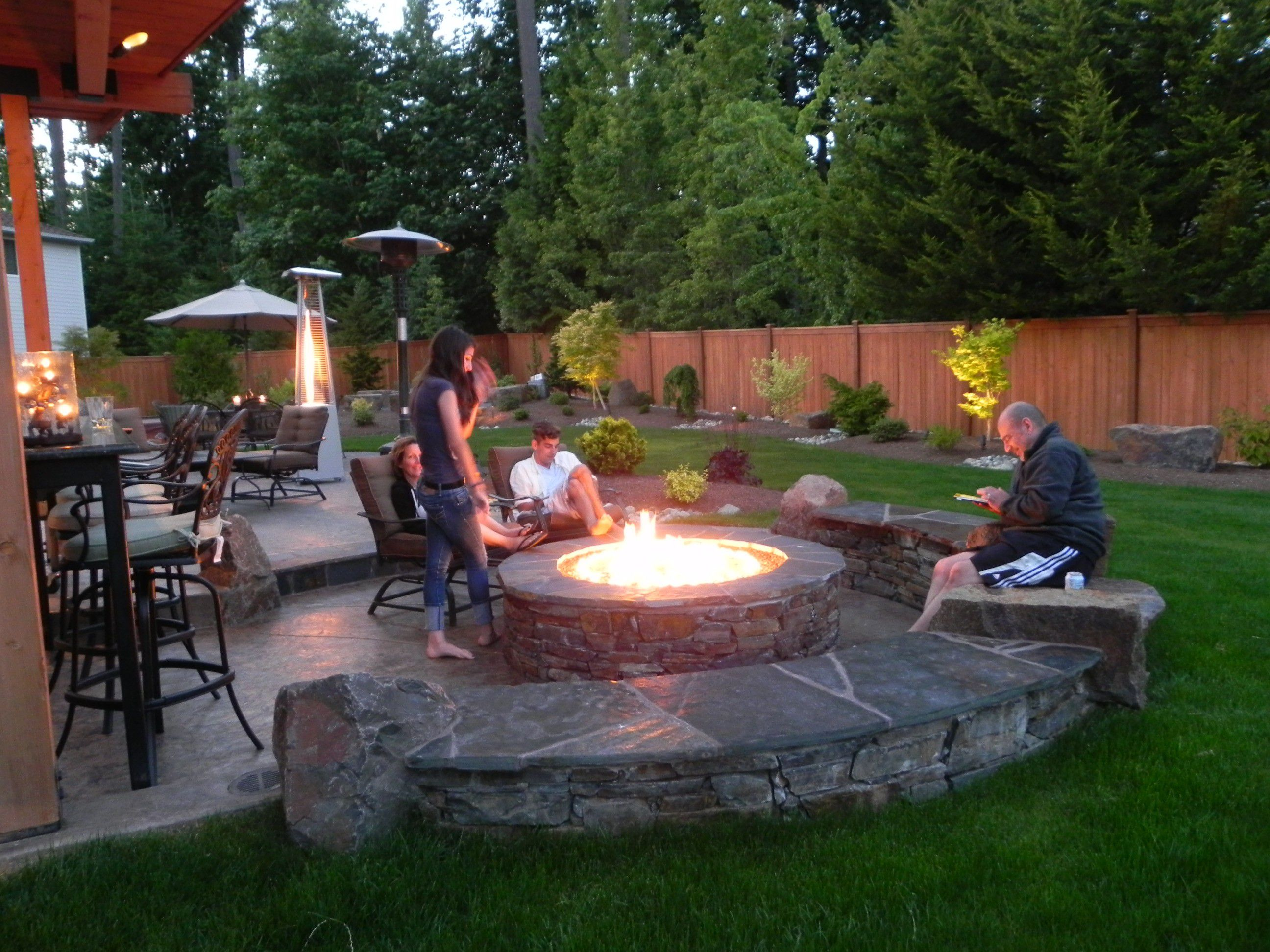 Wide Stone Fire Pit Designs for Natural Patio with Metal Chairs and Stone Bench beside Grass Area