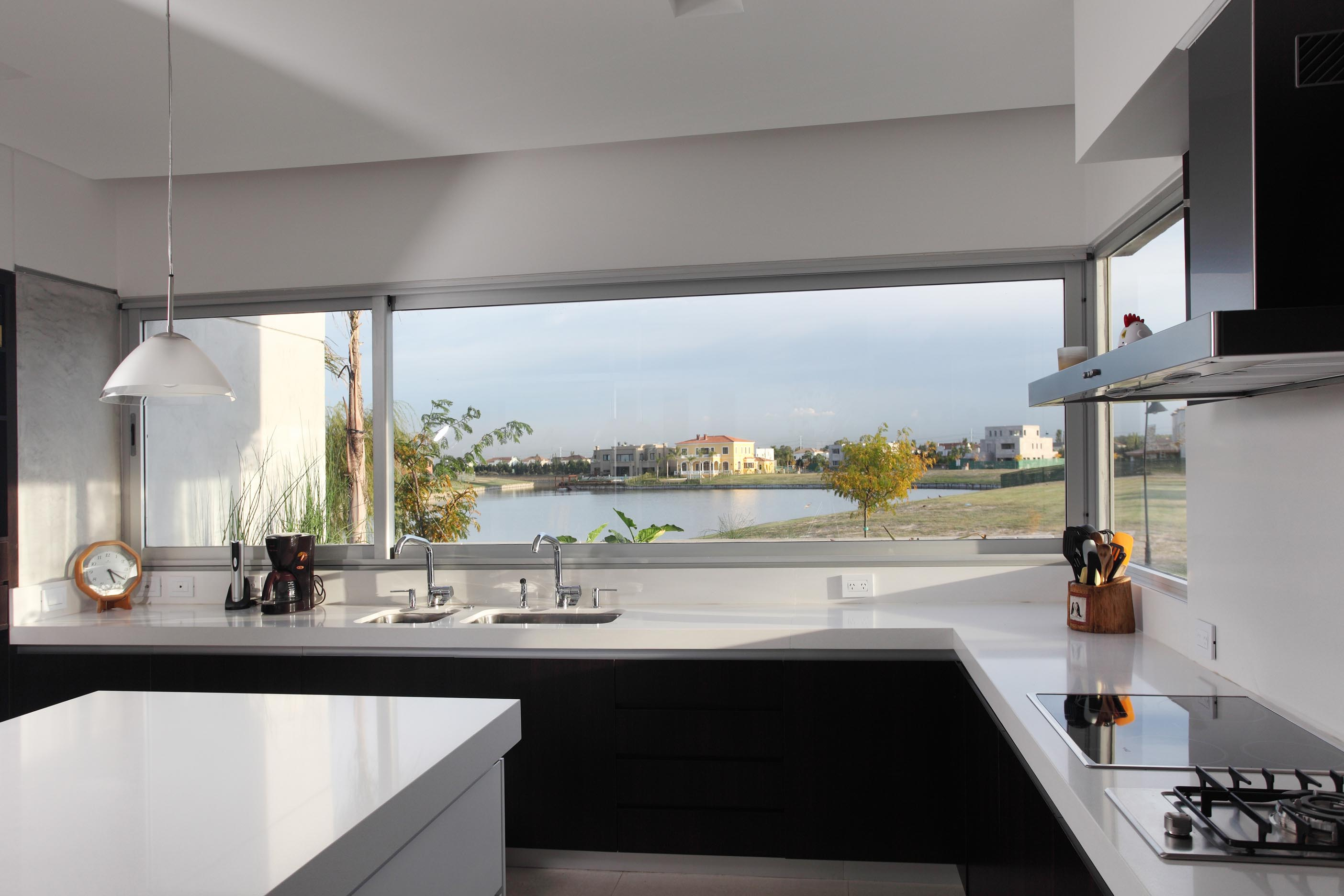 Wonderful Panoramic View from Glass Window in Modern Black and White Kitchen with Long Black Counter and White Island