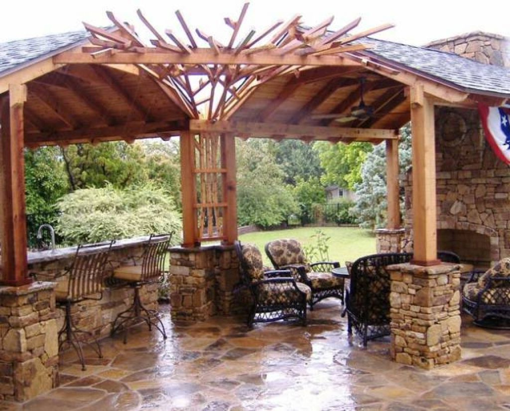 Wooden Pergola and Stone Pillars Used inside Rustic Outdoor Kitchen Plans with Metal Stools