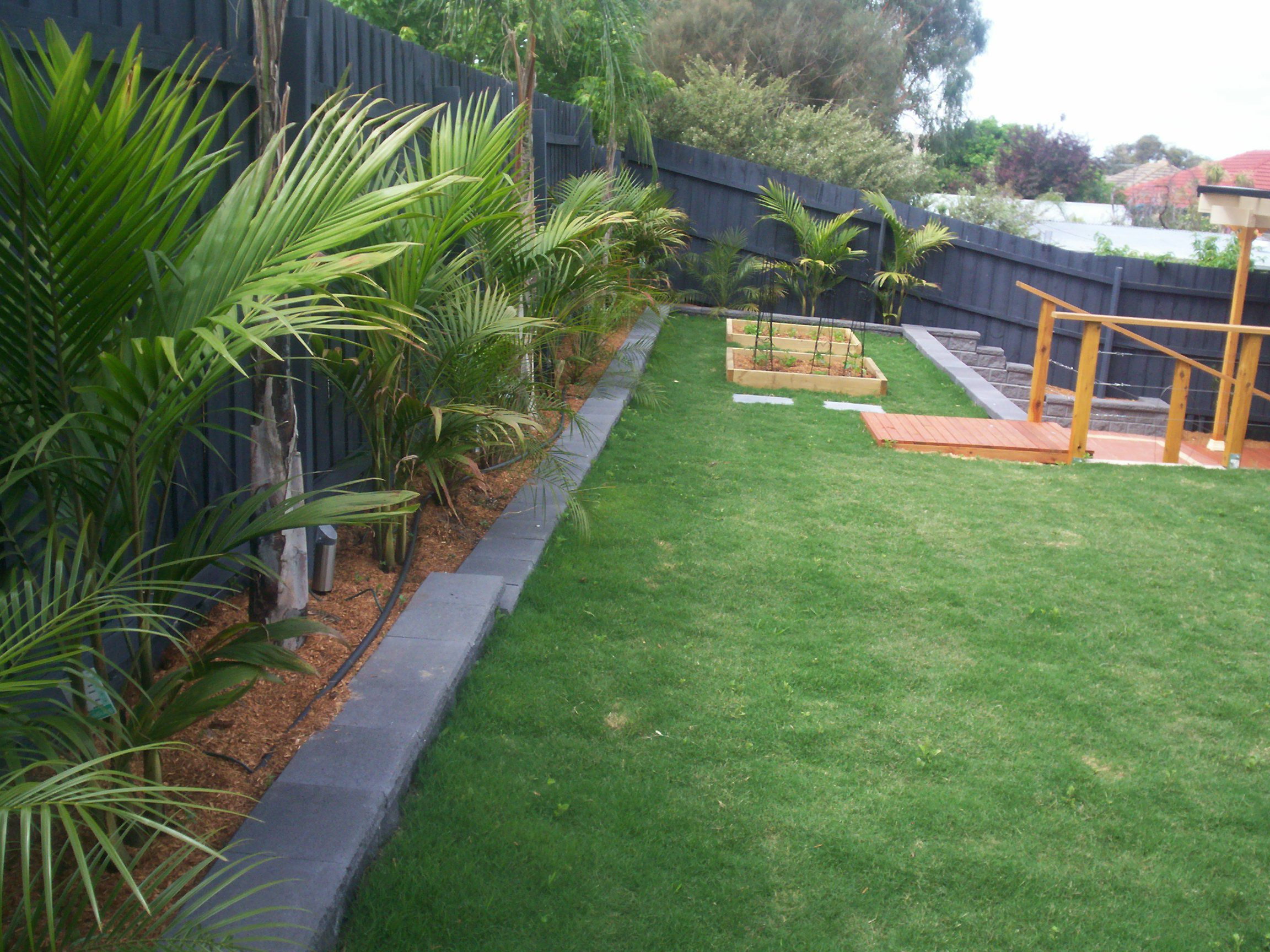 Wooden Stairs and Green Grass Area Completing Interesting Backyard Landscaping Ideas with Dark Wall Fence
