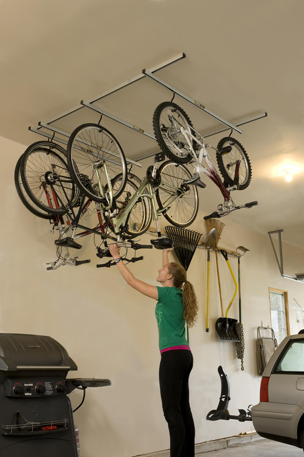 Amazing Design Of The Garage Bike Storage With White Iron Hanging Bike Place At The Ceiling With Three Bikes