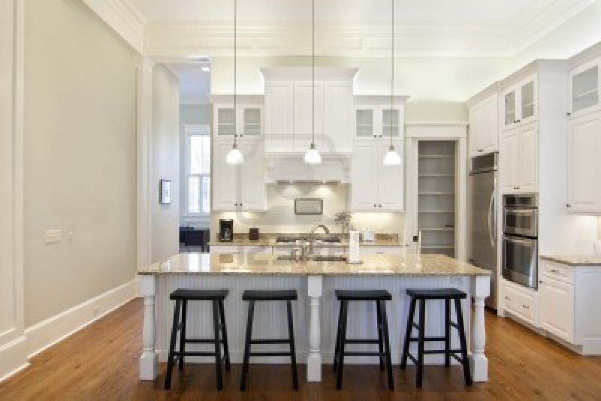 Place Dark Stools and White Island inside Traditional Kitchens with White Cabinets and Bright Lamps
