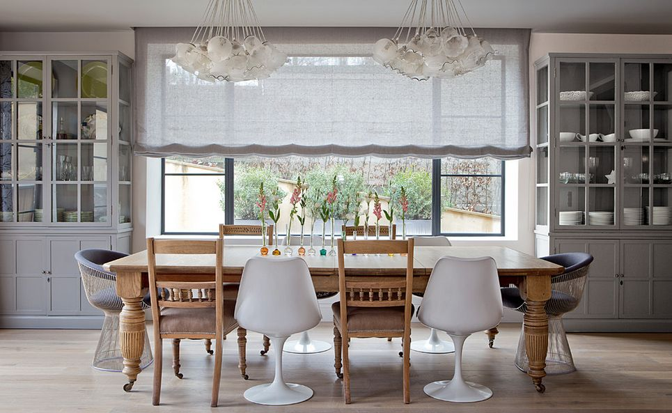 Pleasant Dining Room With Table and Chairs under White Chandeliers