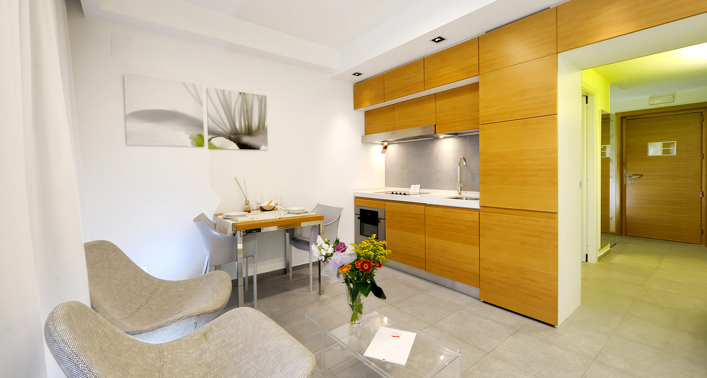 Superb Design Of The Kitchen Areas With Brown Wooden Cabinets And White Wall Added With Grey Sofa As The Small Apartment Furniture